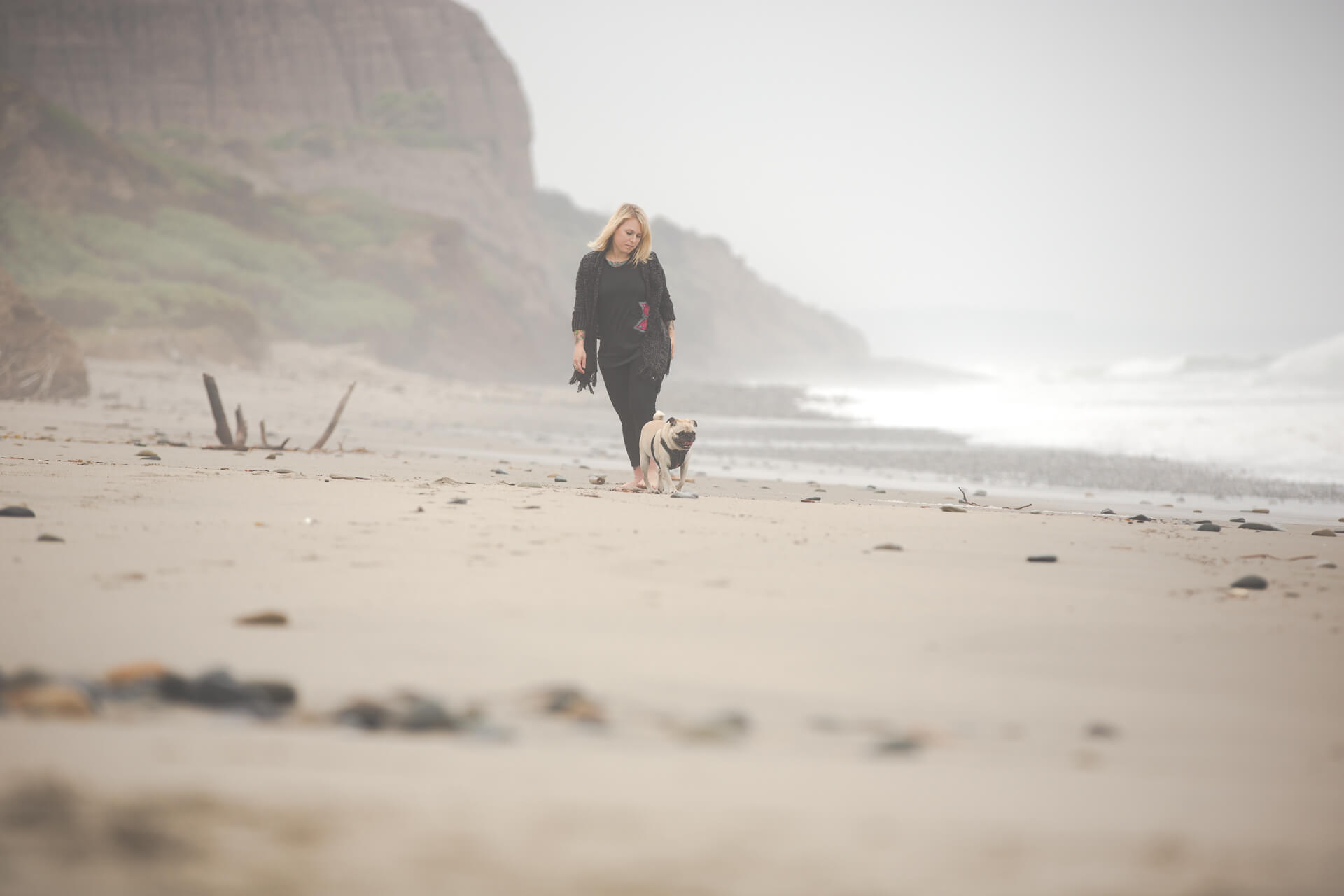 woman walking on the beach with pug